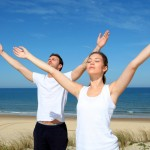 Couple meditating at the beach with arms up